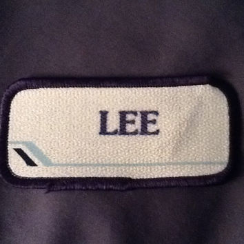 "Lee. An off-white work shirt name patch that says ""Lee"" in blue with blue border"