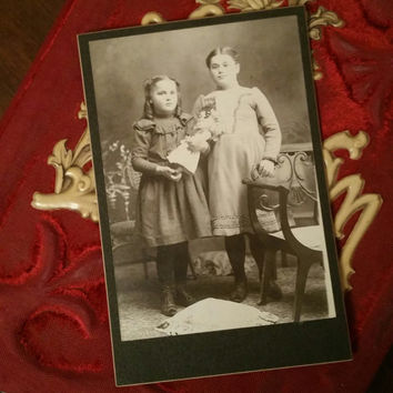 Adorable chubby Victorian sisters with doll cabinet card