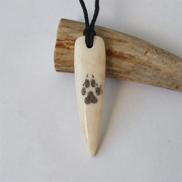 Hand carved elk antler fang with scrimshaw wolf paw