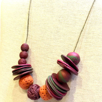 Handmade asymetrical polymer clay necklace, orange, burgundy, maroon,green textured blended beads on adjustable Irish Linen cord