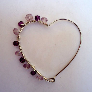 Open heart earrings in silver tone with two shades of amethysts on one side.