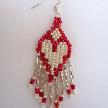 Dangling beaded  earrings with seed beads in the pattern of red hearts and  white background