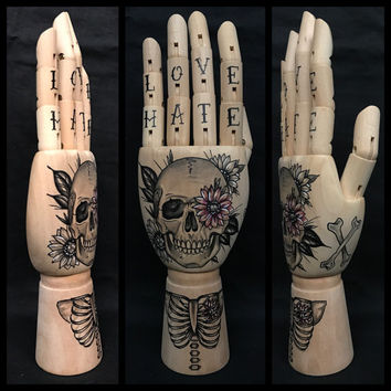 Wooden hand mannequin with original drawings of a skull and flowers, ribcage and crossbones 'tattoo style'