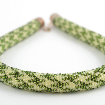 Beige and green handmade beaded cord necklace with geometric pattern