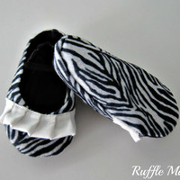 Infant girl shoes made from zebra stripe felt with white ruffle and black elastic straps, size 6-9 mths