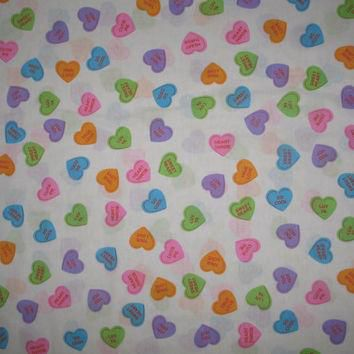 Valentine conversation heart candy fabric with multi-colored hearts on a white backgro