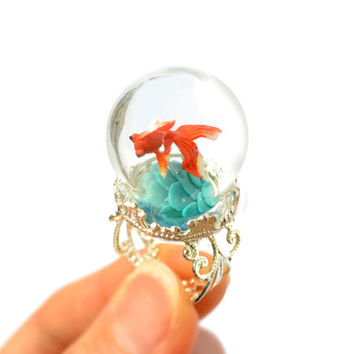 Terrarium ring with tiny goldfish. Miniature under glass globe.