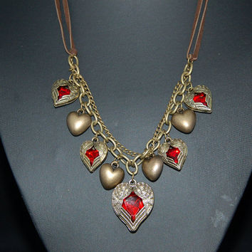 Angel Wing Heart Pendant necklace. Red Stone Hearts Wrapped in Antique Bronze Angel Wings. Suede necklace and bronze chains.