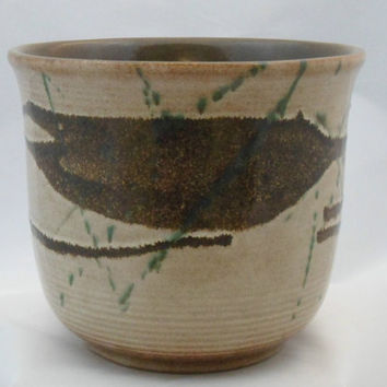 German 1960s planter. Design number 807-17 in abstract design. Green and brown overglaze on natural stone finish