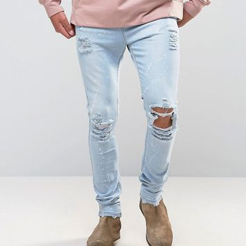 Mennace Skinny Jeans With Paint Splat In Light Wash at asos.com