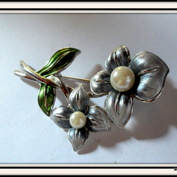 Vintage flower shaped brooch made of silver colored metal and imitation pearls. Retro jewelry / asseccoires made of metal.