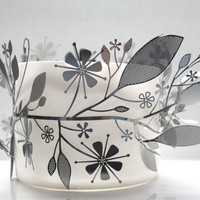 Metal foliage wrapped around a fine bone china vessel