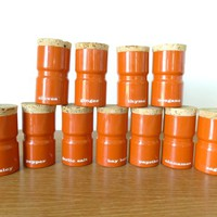 Set of eleven Sam Mann Copco orange enamel spice jars with labels and cork stoppers