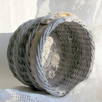 Decorative handmade wicker basket from paper with lace and bow cotton waste