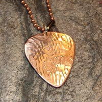 Copper guitar pick pendant with swirling waves of sound