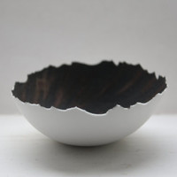 Stoneware vessel made out of fine bone china with black rusty interior with organic edges.