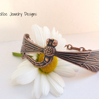 Copper metal engraved dragonfly cuff, with chain and small charm.