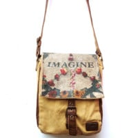 Ever feel like a minimalist? Sling The Slope over your shoulder with this Imagine Mosaic Floral peace sign print on leather Flap, brown leather piping, shoulder straps & stone washed canvas Small Messenger Bag. Unisex style and compact design, Studio Manha