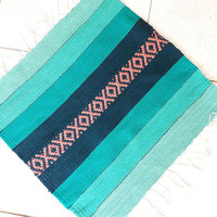 Small handwoven wool rug in green  turquoise colors and pink motifs for your stylish home decor by Rugs N' Bags