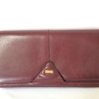 Vintage Bally wine leather clutch bag, party and classic purse with gold tone logo motif.