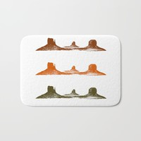 Monument Valley, 3 mountains, 3 colors Bath Mat by Claude Gariepy