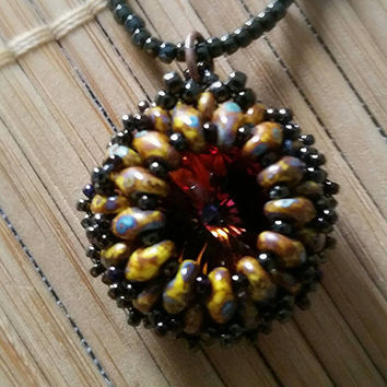 Swarovski crystal is encased in picasso glass beads to make a stunning necklace. Handstiched  together. Looks like an vintage pendant.