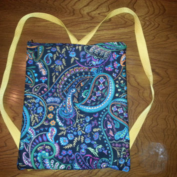 Beautiful Paisley patterned backpack with yellow straps and zipper opening.