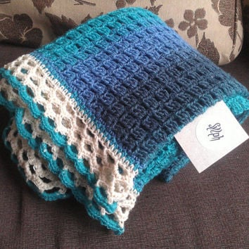 A Crochet Baby Blanket made out of wool yarn in turquoise, blue and ultramarine colors