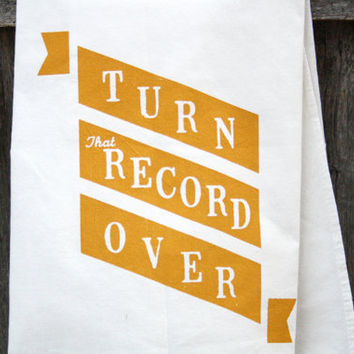 "Kitchen Towel ""Turn That Record Over"" banner print in mustard yellow ink on white towel"