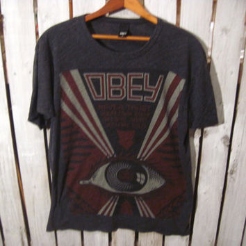 "Obey T-Shirt, Size Medium. ""Never trust your own eyes, believe what you are told."" Reconstruction Available"