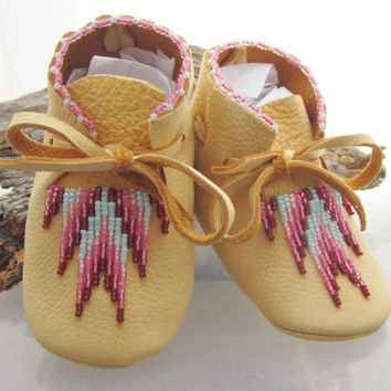Native American handcrafted deer skin baby moccasins with a traditional southwest bead work design.