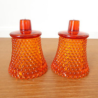 Two orange hobnail glass votive cups, candle cups