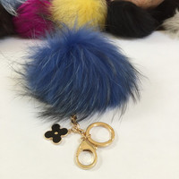 Fur pom pom keychain, bag pendant with flower charm in royal blue with black markings color tone
