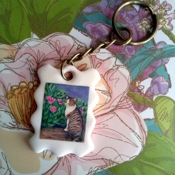 """cat art keychain handmade charm """"a cat looking back at a garden """" polymer clay pendant"""
