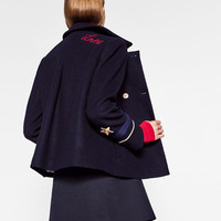 CAPE WITH PATCH DETAIL DETAILS