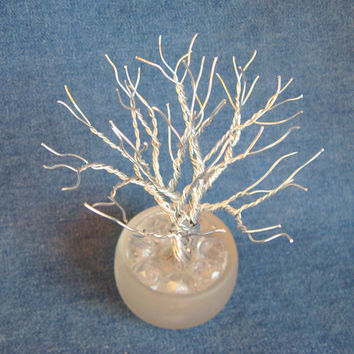 Aluminum wire tree in a repurposed frosted glass candle holder - A twisted wire tree sculpture.
