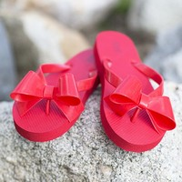 Tell Me A-bow-T It Flip Flops in Red