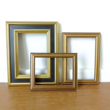 Three small rectangular wood picture frames in various shades of black and gold