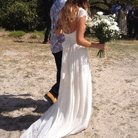 Capped sleeves, low scooped back with rosette trim and train. French lace and silk chiffon wedding dress