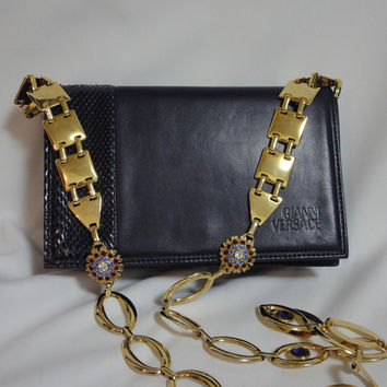 Vintage Gianni Versace navy leather clutch shoulder purse with snake skin and golden parts and crystal, blue, and red jewel stones motifs.