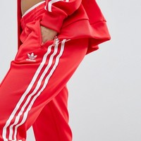 adidas Originals adicolor Three Stripe Track Pants In Red at asos.com